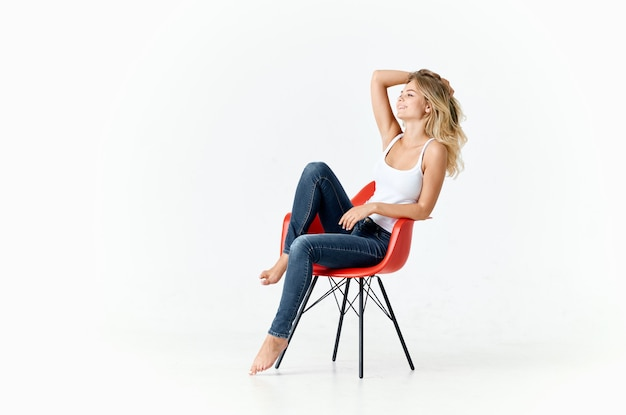 Woman on red chair posing on light background fashion