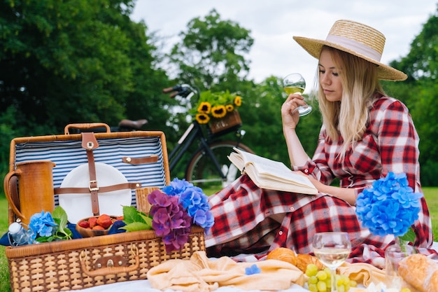 Woman in red checkered dress and hat sitting on white knit picnic blanket reading book and drinking wine