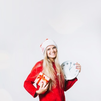 Woman in red clothes with clock and gift box