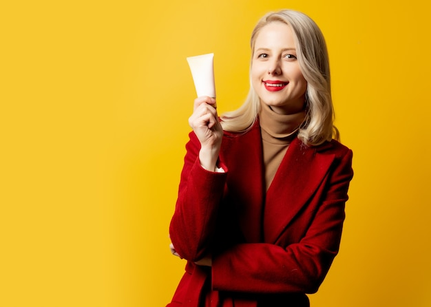 Woman in red coat with cream tube on yellow wall