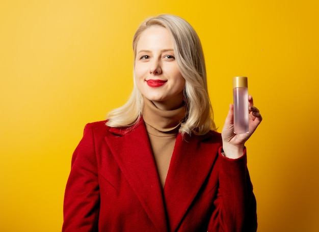 Woman in red coat with lotion bottle on yellow wall