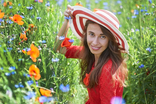 Woman in red dress and a big red striped hat sitting in beautiful flowering poppy field