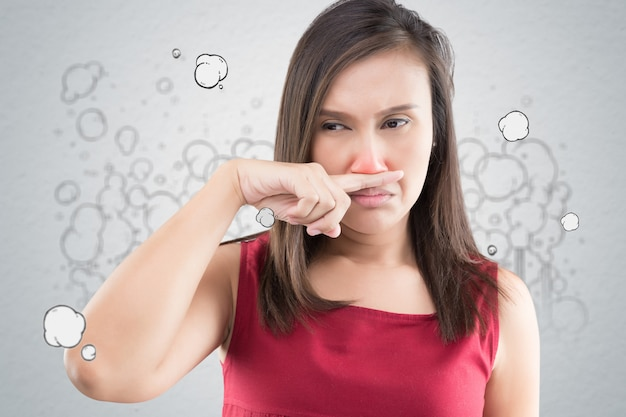 A woman in a red dress catches her nose because of a bad smell
