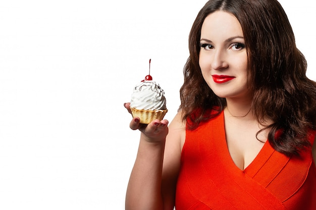 A woman in a red dress holding a cake