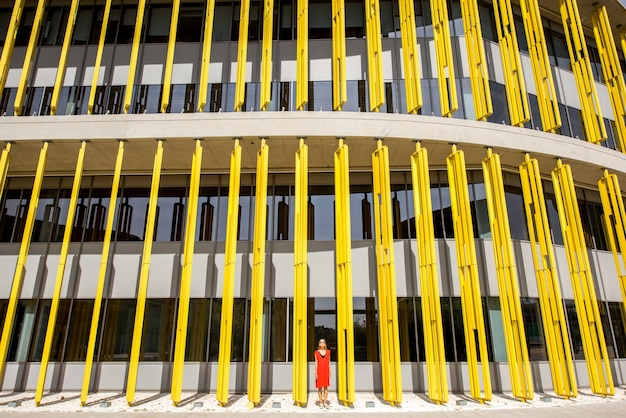 Woman in red dress on the modern yellow building wall background. abstract geometric composition