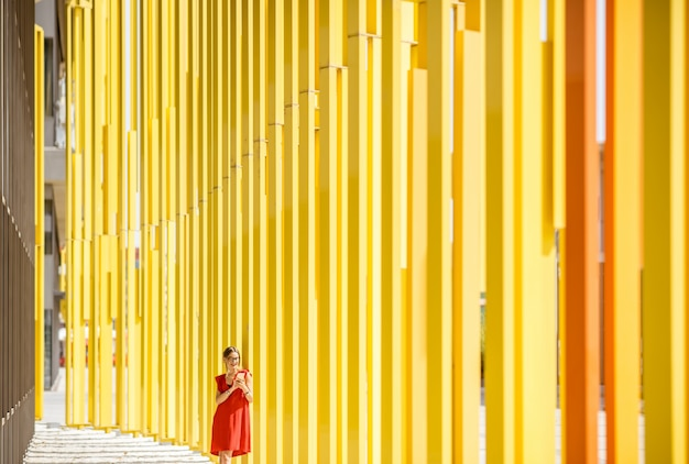 Woman in red dress on the modern yellow building wall background. general plan with abstract geometric composition