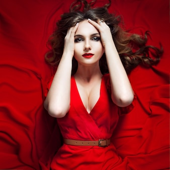 Woman in red dress posing with waving fabric