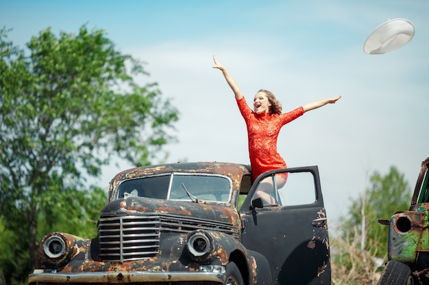 Woman in a red dress rise in an old car