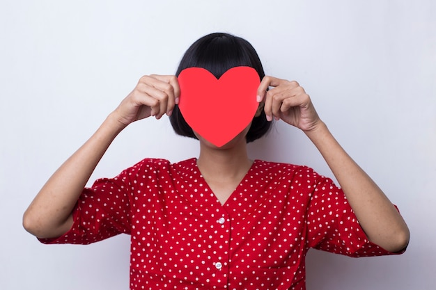 Woman in red dress shows heart shape in the concept of love and valentine