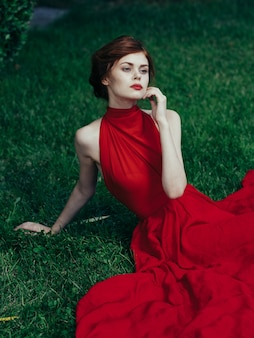 Woman in red dress sits on the grass charm and luxury exotic style park.