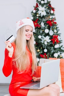 Woman in red dress sitting with laptop and card near christmas tree