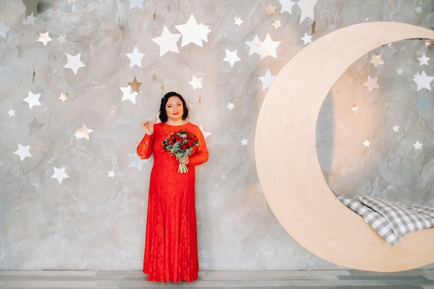 A woman in a red dress stands and holds a bouquet of red roses and strawberries in a fabulous studio.
