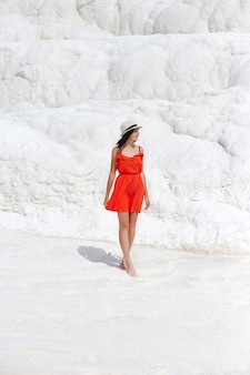 Woman in a red dress stands on white travertines