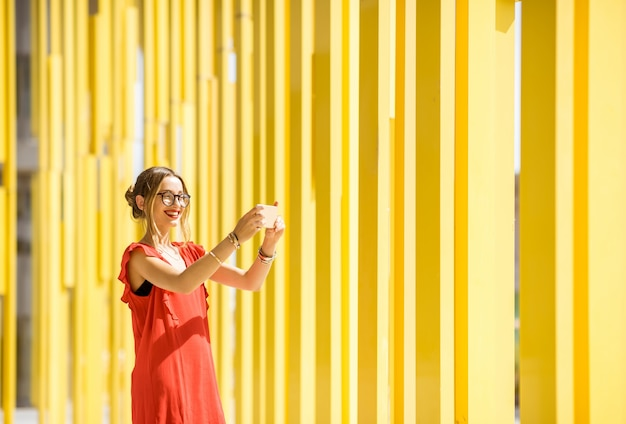 Woman in red dress taking selfie photo on the modern yellow building wall background