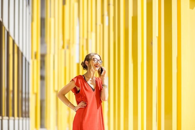 Woman in red dress talking with phone on the modern yellow building wall background