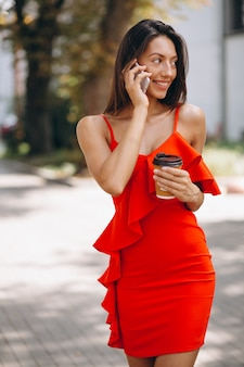 Woman in red dress using phone and drinking coffee