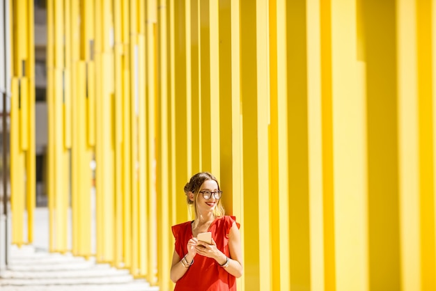 Woman in red dress using phone on the modern yellow building wall background. abstract geometric composition
