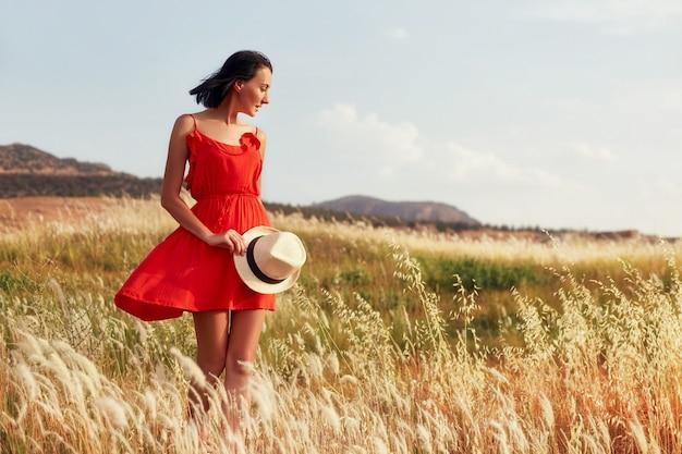 Woman in a red dress walking on the field