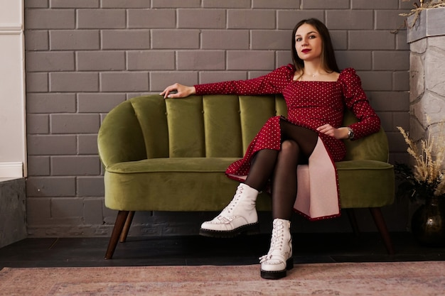 Woman in a red dress and white shoes on a green sofa