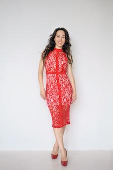 Una donna in un vestito rosso con il trucco sui sorrisi