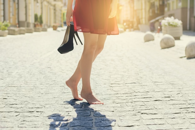 Woman in red elegant dress, holding high heel shoes in hand and walking in the city barefoot. close up cropped photo. sun beam light rays shine sunburst burst  shiny flare effect glare sparkle