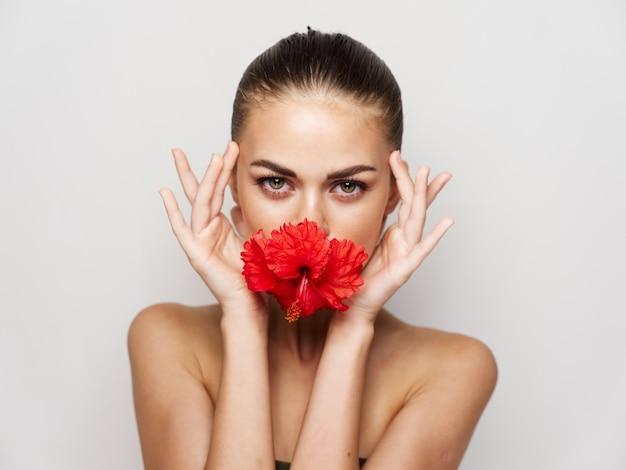 女性の赤い花の化粧品の装飾のトリミングされたビュー