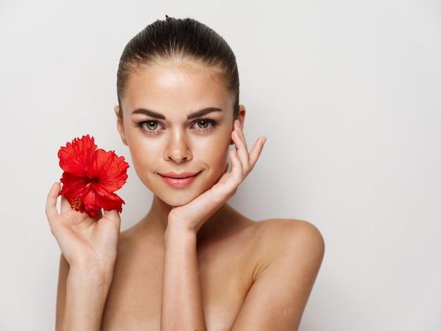 裸の肩の上の女性の赤い花は明るい背景を魅了します