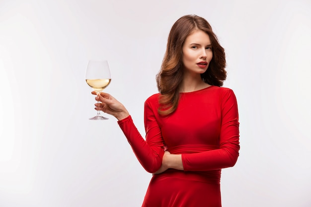 Woman in red gown with champagne glass on white