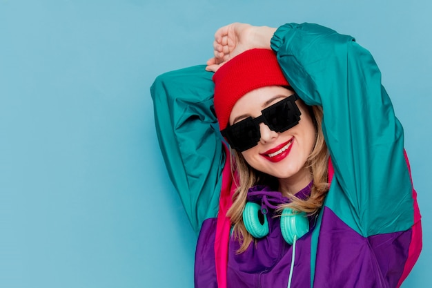 Woman in red hat, sunglasses and suit of 90s with headphones