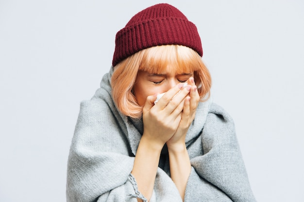 Woman in red hat, warm scarf with paper napkin sneezing, experiences allergy symptoms
