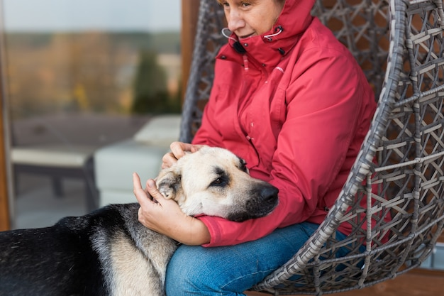 A woman in red jacket plays and petting a shepherd dog while sitting in a wicker chair