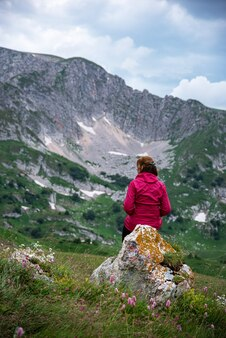 A woman in a red jacket sits on a rock in a mountain valley and looks into the distance
