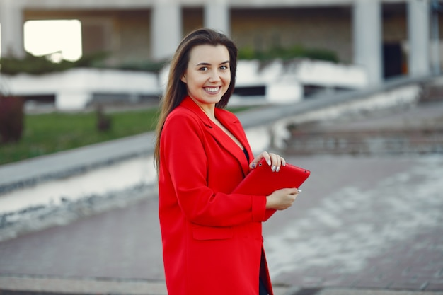 Woman in red jacket using a tablet