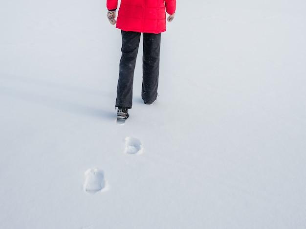 Woman in the red jacket walking on snow, footprints in snow, behind.