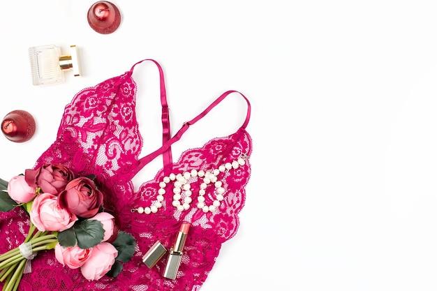 女性の赤いレースのランジェリー、花、メイクアップ
