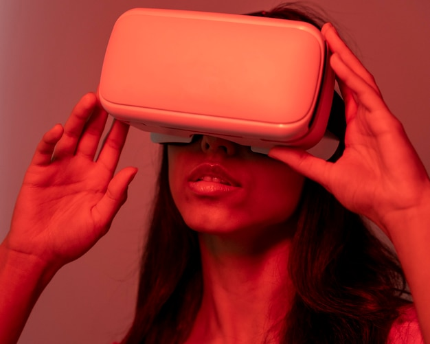 Woman in red light using virtual reality headset
