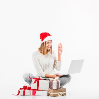 Woman in red santa hat making video call