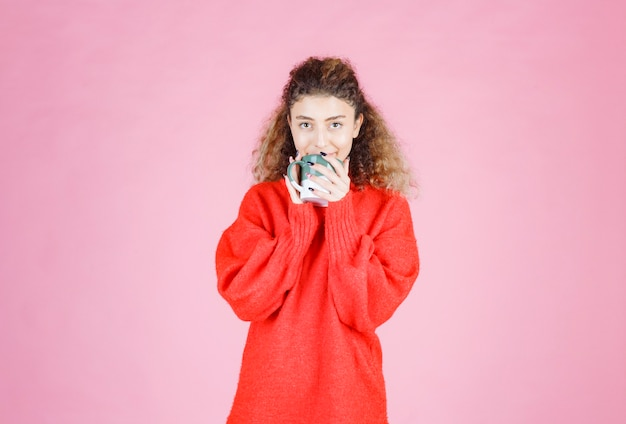 Donna in camicia rossa che beve una tazza di caffè.