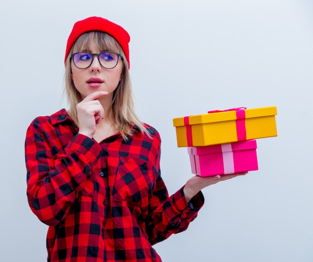 Woman in red shirt and hat holding holiday gift boxes