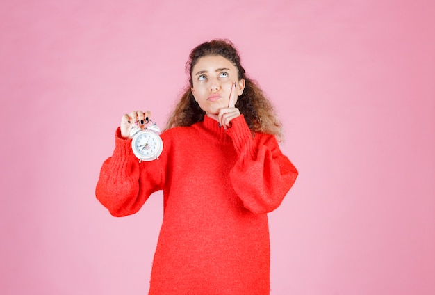 Woman in red shirt holding alarm clock and thinking.