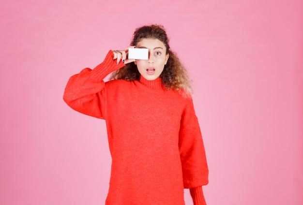 Donna in camicia rossa che tiene un biglietto da visita al suo occhio.