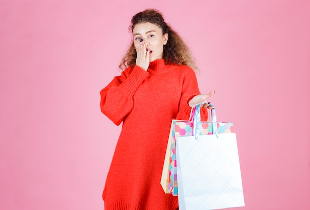 Donna in camicia rossa che tiene più borse della spesa colorate.