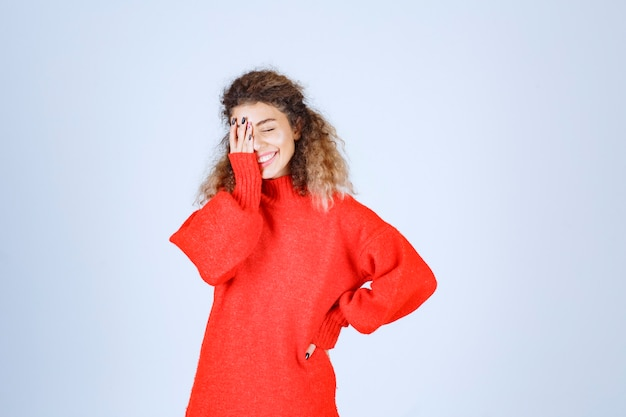 Woman in red shirt looking across her fingers and laughing.