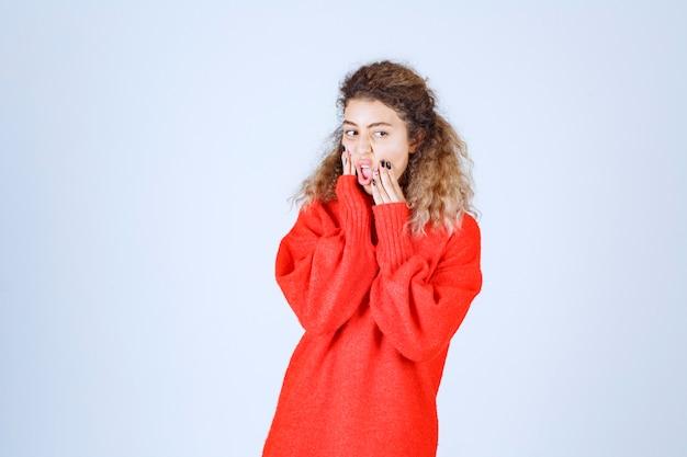 La donna con una camicia rossa sembra pessimista o triste.