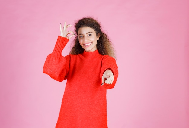 Donna in camicia rossa che nota qualcuno avanti e invia energia positiva.