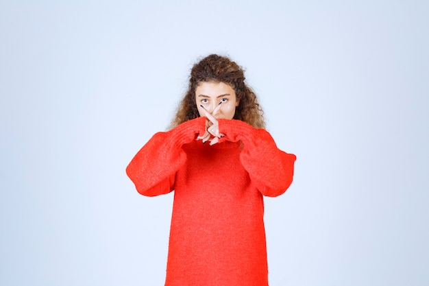 Woman in red shirt pointing her mouth and asking for silence.