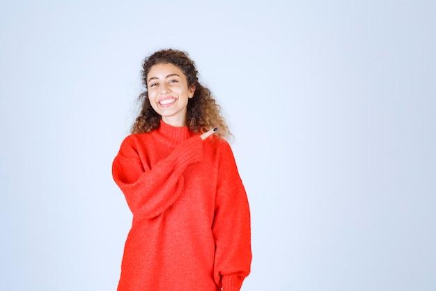 Donna in camicia rossa che punta a qualcuno o da qualche parte con la faccia emotiva sul blu.