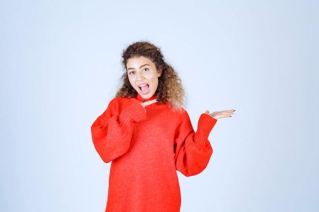 Donna in camicia rossa che indica qualcuno sulla destra.