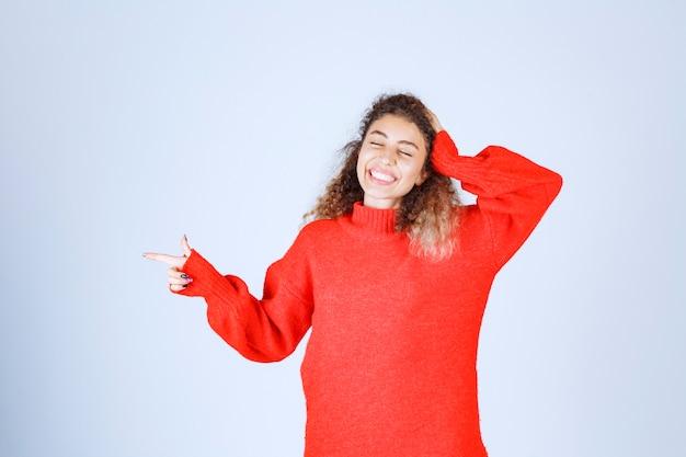 Donna in camicia rossa che indica qualcosa a sinistra.
