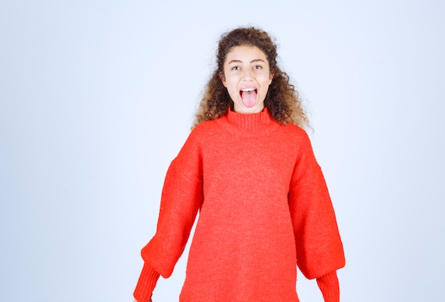 Woman in red shirt putting her tongue out and screaming.